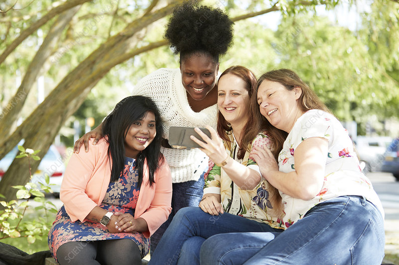 Happy female friends using smart phone