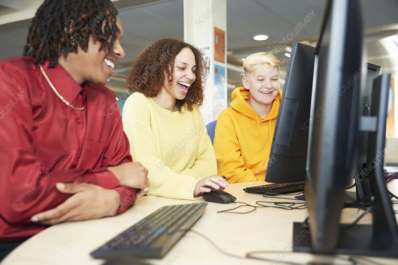 College students studying together at computer in library