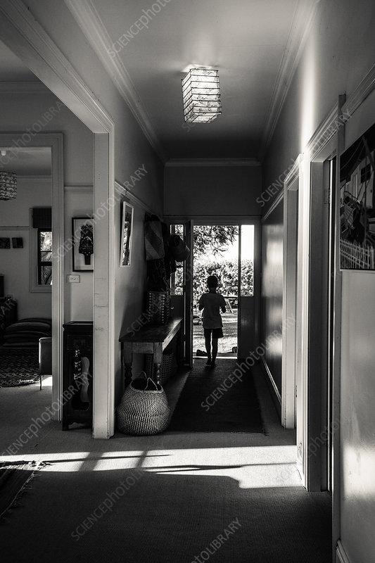 Boy standing in home corridor