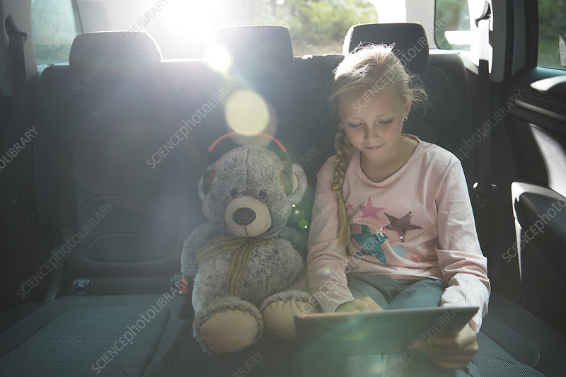 Girl with teddy bear using tablet in back seat of car