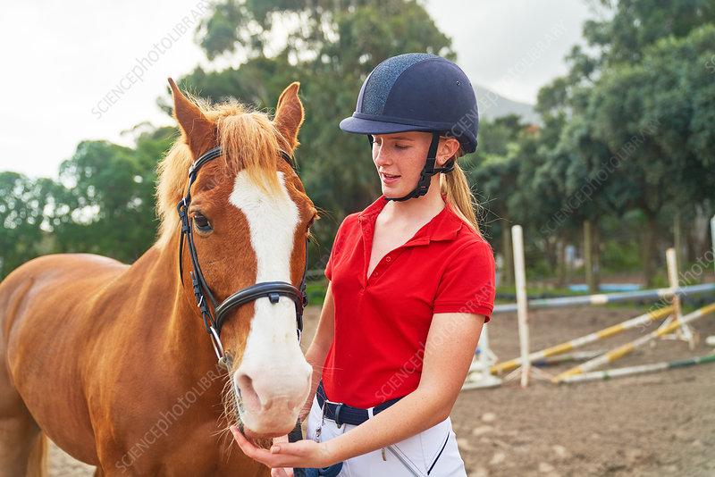 Teenage girl in equestrian helmet with horse in paddock
