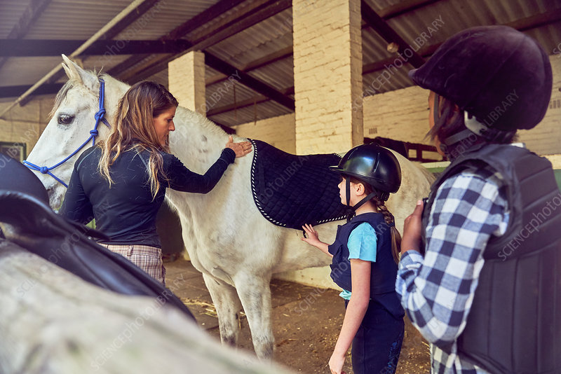 Instructor helping girls prepare for horseback riding