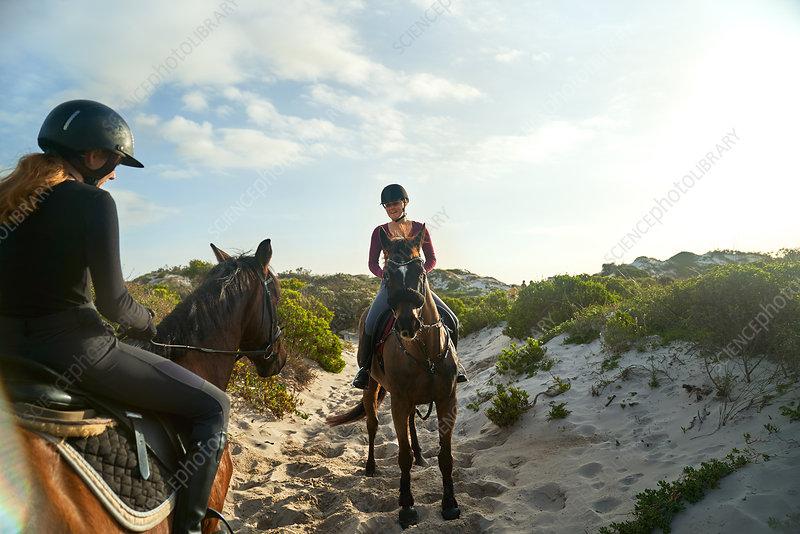 Young women horseback riding on sunny beach