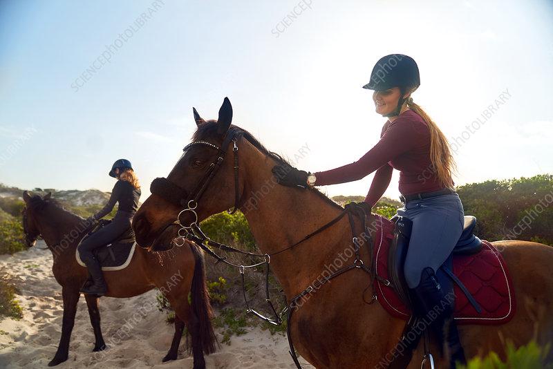 Young women horseback riding on beach