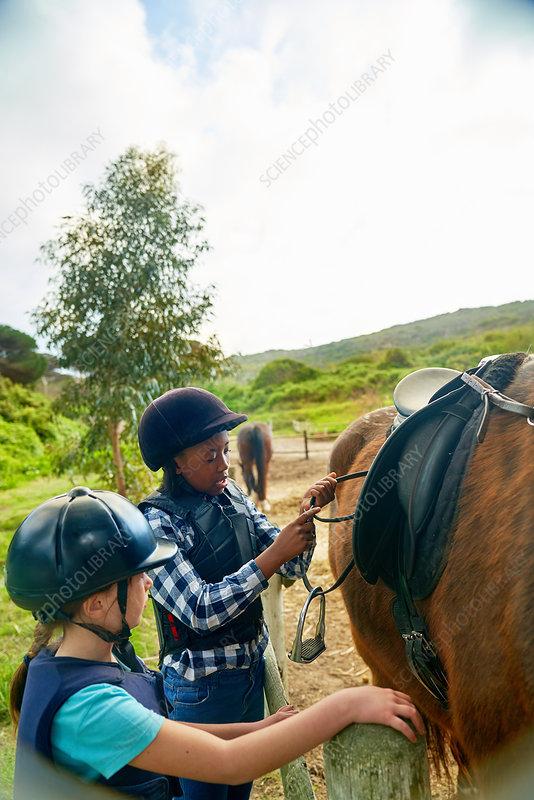 Girls adjusting stirrups for horseback riding