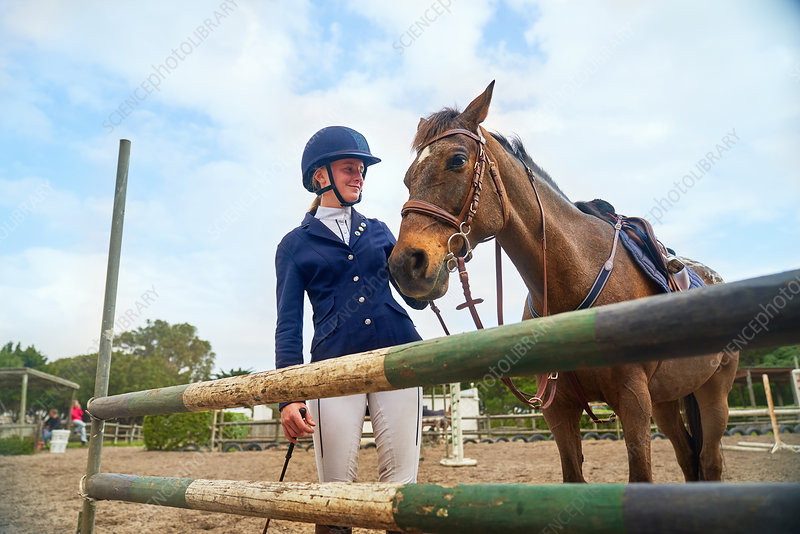 Girl in equestrian helmet with horse at obstacle