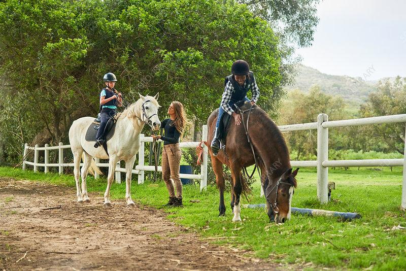 Girls preparing for horseback riding lesson