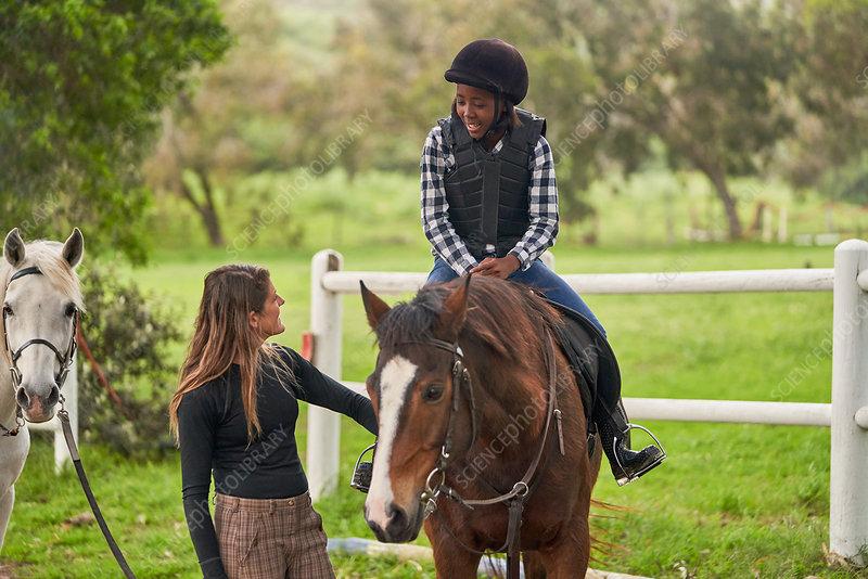 Instructor teaching horseback riding to girl