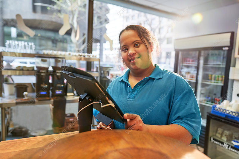 Portrait young woman with Down Syndrome working in cafe