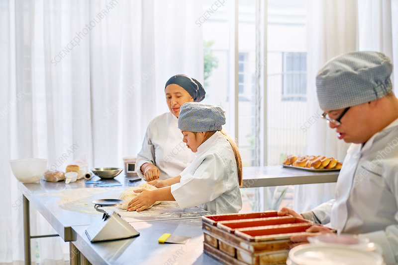 Chef helping female student with Down Syndrome in kitchen
