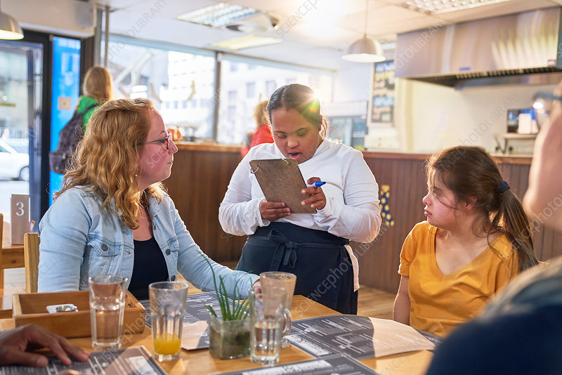 Young server with Down Syndrome taking customer order