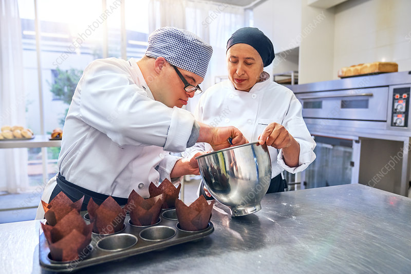 Chef helping student with Down Syndrome baking muffins
