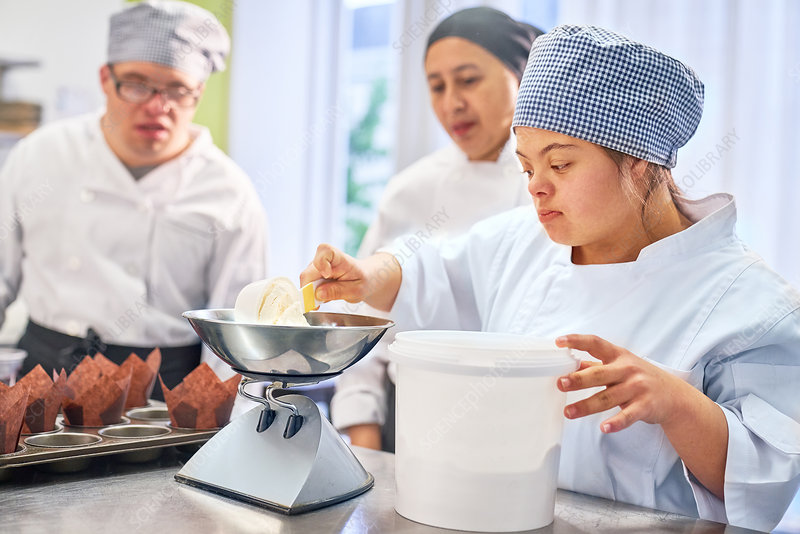 Young woman with Down Syndrome learning to bake in kitchen