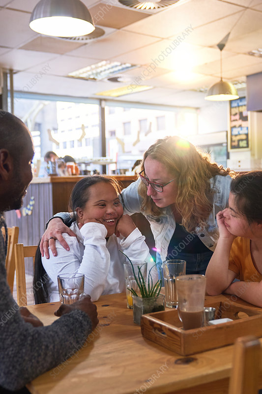 Mentor and young women with Down Syndrome talking in cafe