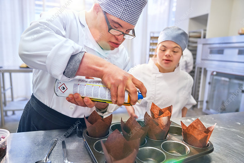 Students with Down Syndrome baking muffins in kitchen