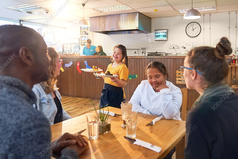 Young server with Down Syndrome serving dessert in menu