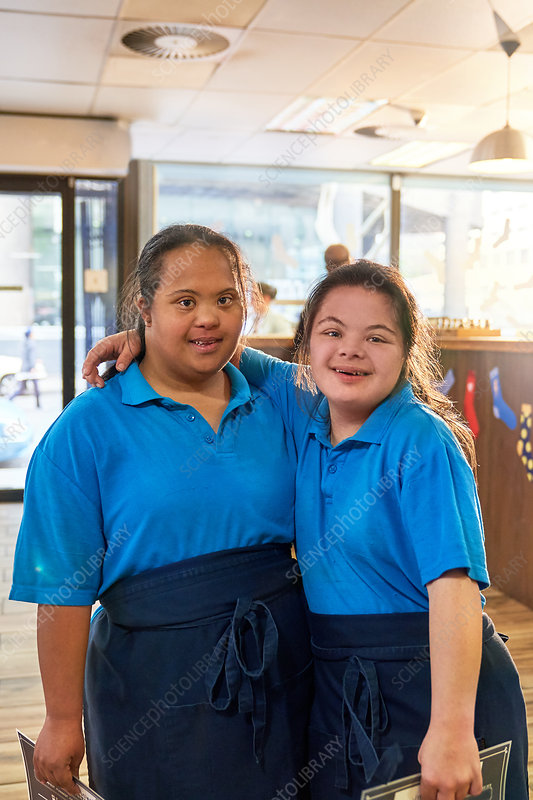 Portrait young women with Down Syndrome working in cafe