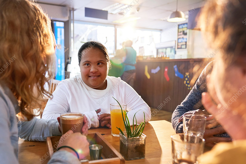 Woman with Down Syndrome talking with friends in cafe