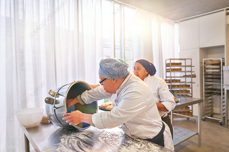 Chef and student with Down Syndrome baking in kitchen