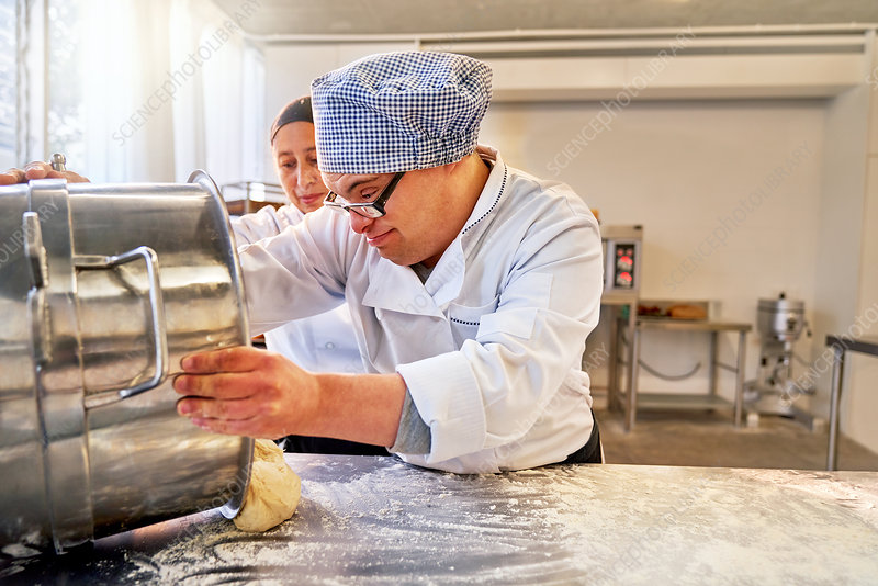 Young male student with Down Syndrome baking in kitchen