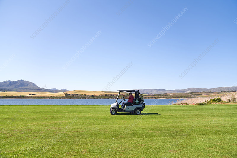 Male golfer driving golf cart along lake