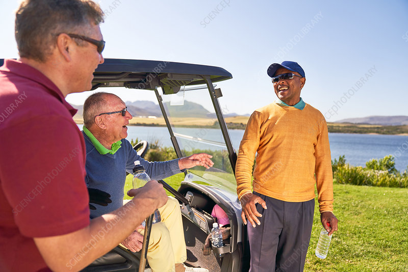 Male golfer friends talking and laughing at golf cart