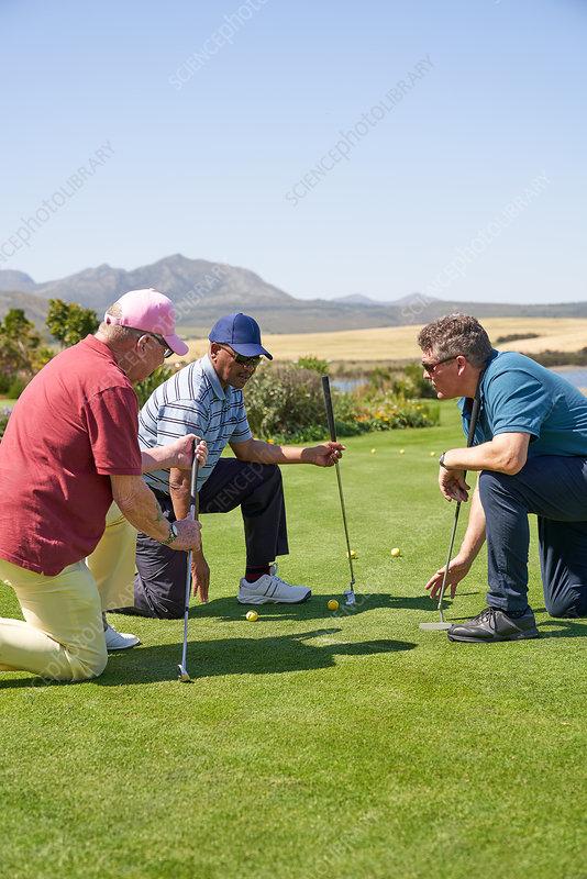 Male golfers kneeling on putting practice green