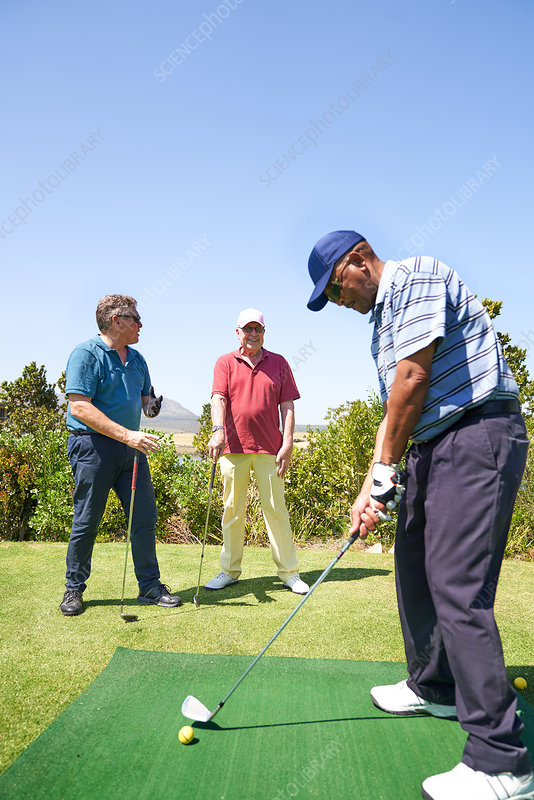 Male golfer practicing swing at golf driving range