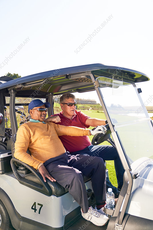 Mature male golfers riding in golf cart