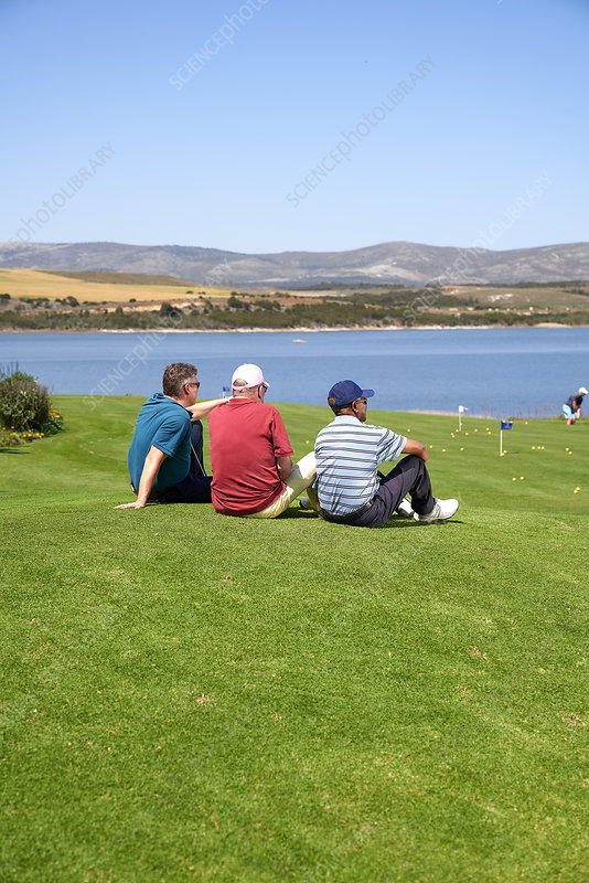 Male golfers taking a break resting in grass