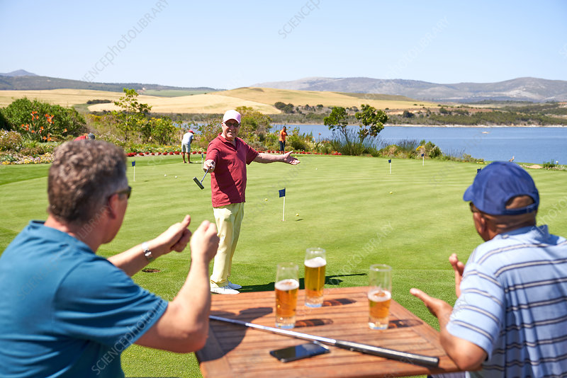 Happy golfers drinking beer and practicing