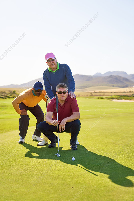 Male golfers planning putt shot putting green