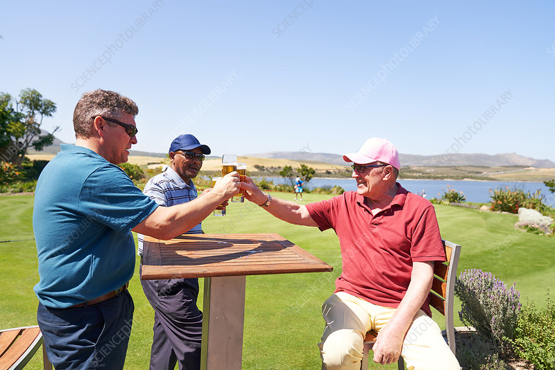 Mature golfers drinking beer on sunny golf clubhouse patio