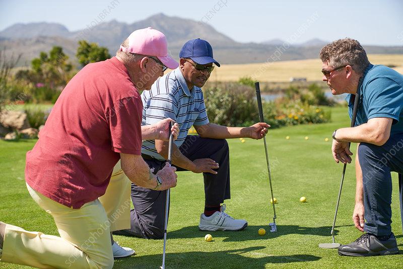 Male golfers kneeling and talking