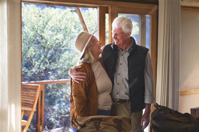 Happy senior couple hugging in safari lodge hotel room