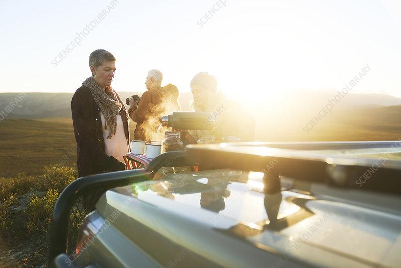 Safari tour group enjoying hot tea at sunrise