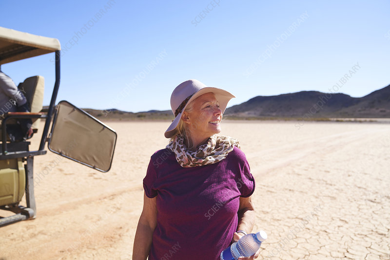 Senior woman on safari in sunny arid desert South Africa