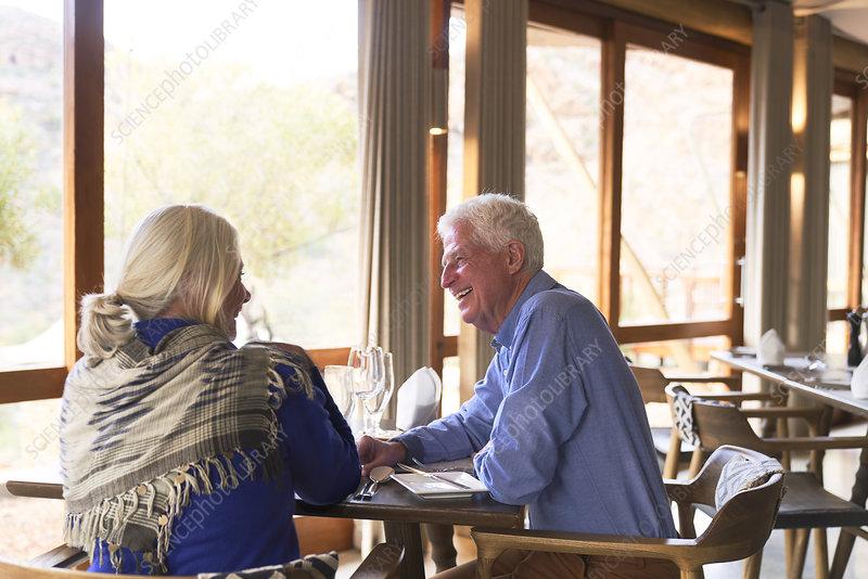 Happy senior couple dining in restaurant