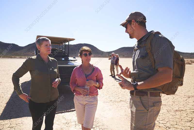 Guide talking with women in sunny desert South Africa