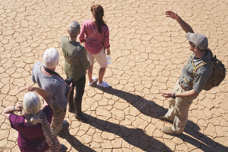 Guide talking with group on sunny cracked earth