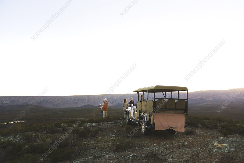 Group and off-road vehicle on remote hill at sunrise