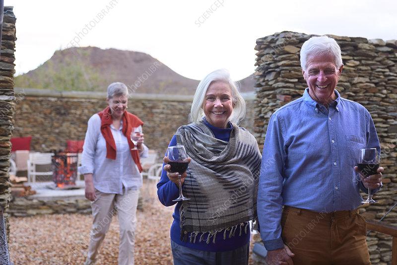 Portrait happy senior couple drinking wine on hotel patio