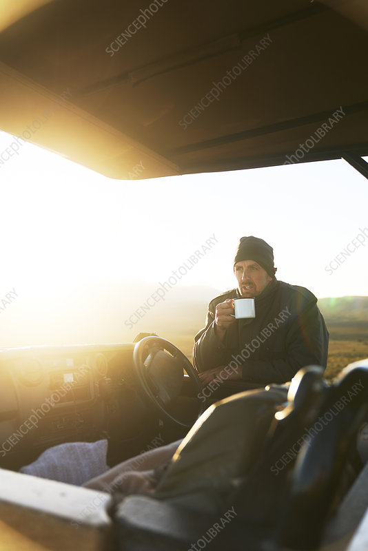 Guide drinking tea at off-road vehicle at sunrise