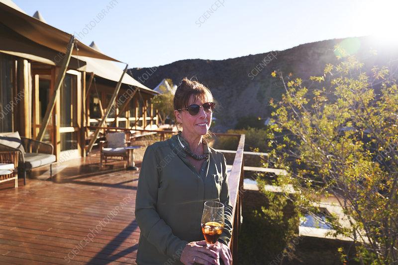 Portrait mature woman on sunny hotel balcony