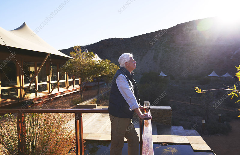 Serene senior man relaxing on sunny safari lodge balcony