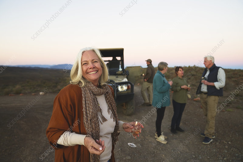 Portrait happy senior woman drinking champagne on safari