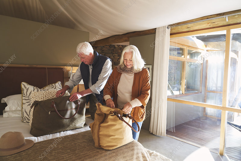Senior couple unpacking bags in hotel room