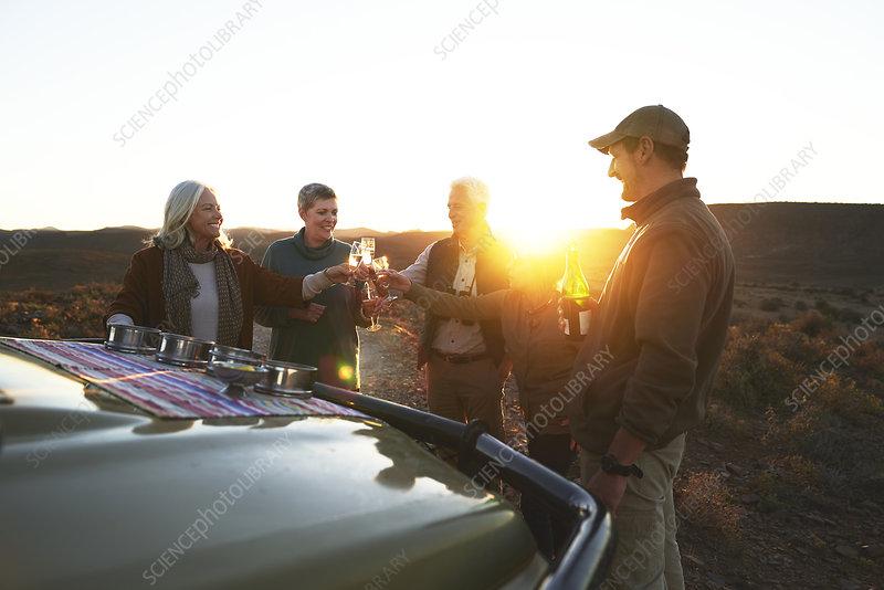 Safari tour group toasting champagne glasses on sunset