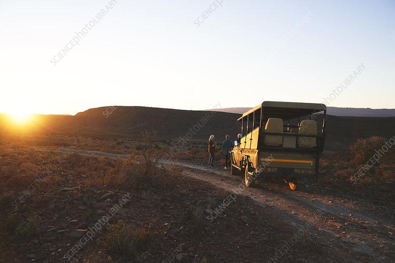 Safari vehicle and tourists at sunset roadside
