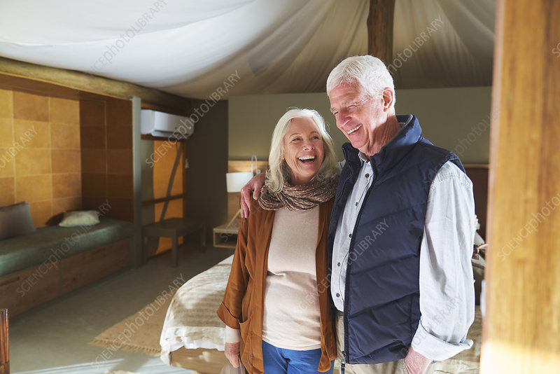 Happy senior couple laughing in hotel room